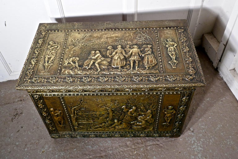 Very large French embossed brass log box, with country scenes  This is a large chest is made in brass with a wooden lining, the beaten brass is embossed with country scenes celebrating the harvest on the top and front, on the sides the scenes are