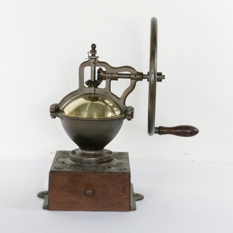 This very large late 19th century iron coffee grinder was originally used in a French bistro. Marked Peugeot Freres Brevetes SGDG, and the number 4, this coffee grinder was the second largest in size ever produced by Peugeot Freres. Its brass cover