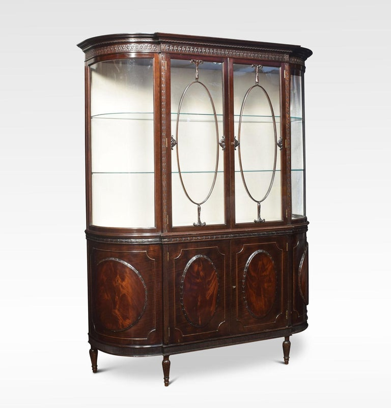 Mahogany bow ended display cabinet the cornice having Greek Key moldings above two large rectangular doors, flanked by two bowed glazed sides. The base section having four flame mahogany oval panels with two central doors enclosing large storage