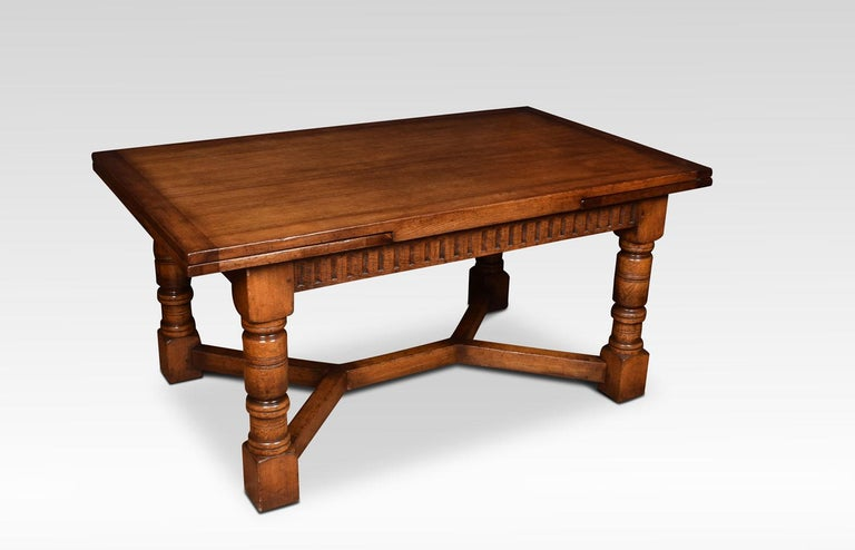 Oak draw leaf refectory table, the rectangular solid oak top above two pullout / pull-out ends, to the ed frieze above massive turned gun barrel legs joined by a double Y-shaped stretcher. Dimensions Height 30.5 inches Width 66 inches when open
