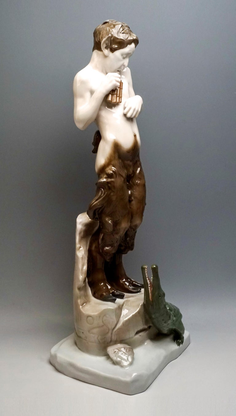 Admirable and very rare Art Nouveau Figurine by Rosenthal. The faun stands frightened on a broken piece of ruins with Egyptian inscriptions, holding a panpipe in his right hand, a small crocodile at his feet, which looks up at him with open mouth