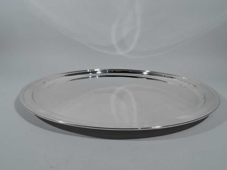 Very large sterling silver serving tray. Made by Tiffany & Co. in New York. Circular with molded rim. The traditional form super-sized. Hallmark includes postwar pattern no. 23542. Weight: 106 troy ounces.