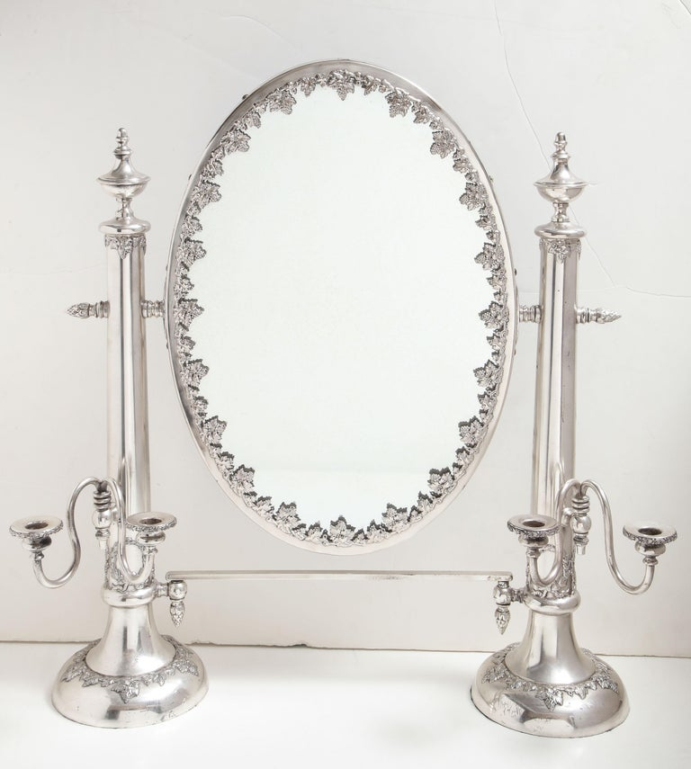 Very large, Victorian, Sheffield silver plated table mirror, Lawrence B. Smith Co., Boston, circa 1895. Measures: 26 inches high (at highest point) x 25 inches wide (from candleholder to candleholder) x 6 1/2 inches deep. Mirror itself, which