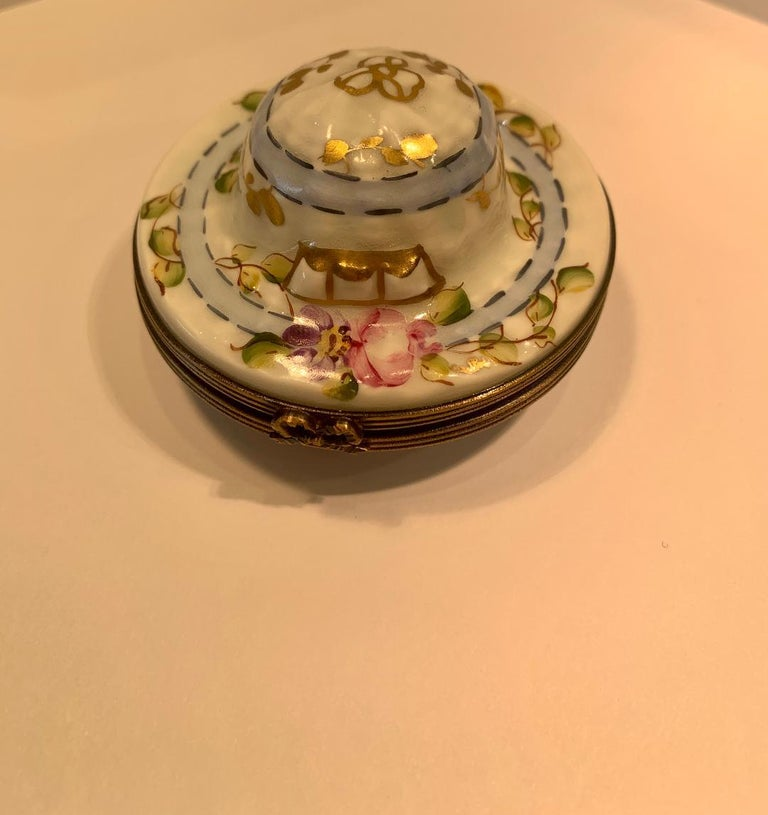 Very pretty, Limoges porcelain miniature hat shaped trinket box is handmade and hand painted in France and features vining floral motif with rich 24-karat gold accents. Box features antiqued gold gilt metal fittings and trim with a sweet