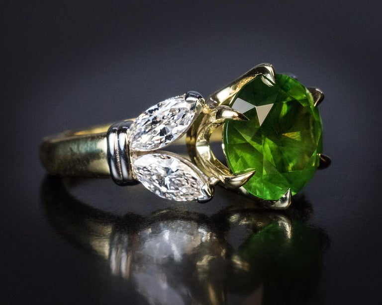 This contemporary ring features a very rare 4.98 ct Russian demantoid from the Ural Mountains. The demantoid is flanked by two pairs of bright white (E-F color, VS clarity) marquise cut diamonds.  The demantoid measures 10.08 x 10.05 x 6.72 mm and