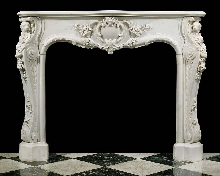 Irish water spaniels A rare and remarkable English Rococo Statuary Marble antique chimneypiece with richly and intricately carved floral and rocaille decoration. The boldly conceived and executed central cartouche bordered by both subtle and high