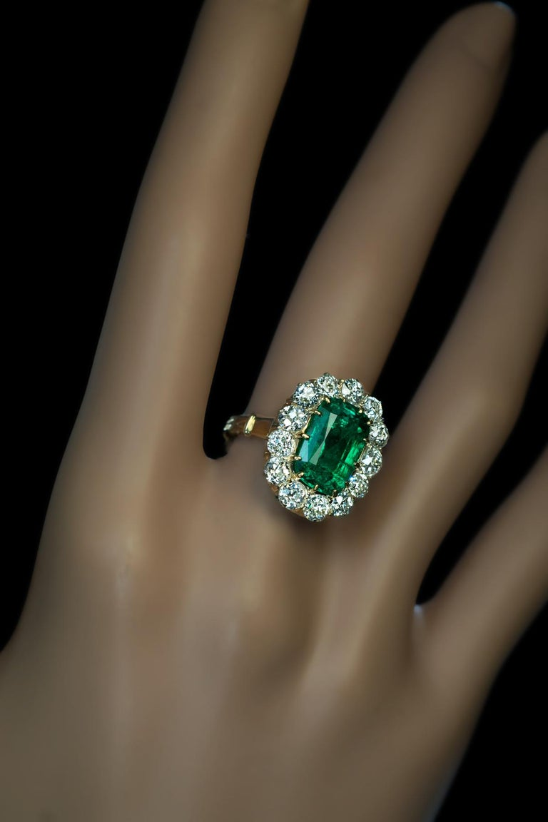 This antique Russian ring dated '1871', features a very rare Russian (the Ural Mountains) lush bluish green emerald (3.24 Ct) surrounded by bright white old mine cut diamonds.  The ring is crafted in 14K yellow gold. The diamonds are set in silver