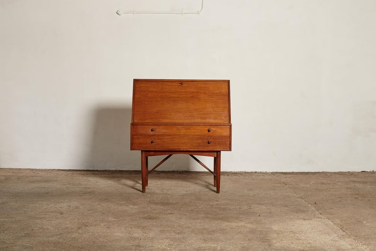 Very rare Ib Kofod Larsen secretary desk / Bureau, made by PA Pedersen, 1954, Denmark. Made of teak, with 2 drawers, a drop leaf, several smaller drawers and a drop down mirror inside.   Measures: H 115cm W 100cm D 50cm  Literature: DKH Print,