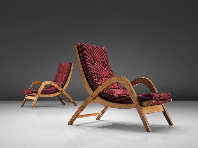 Neil Morris for H. Morris, lounge chairs, burgundy red upholstery and plywood, Scotland, 1940s.   These wavy, elegant armchairs have both a high back and high armrests and together create the high character of these very large lounge chairs. The