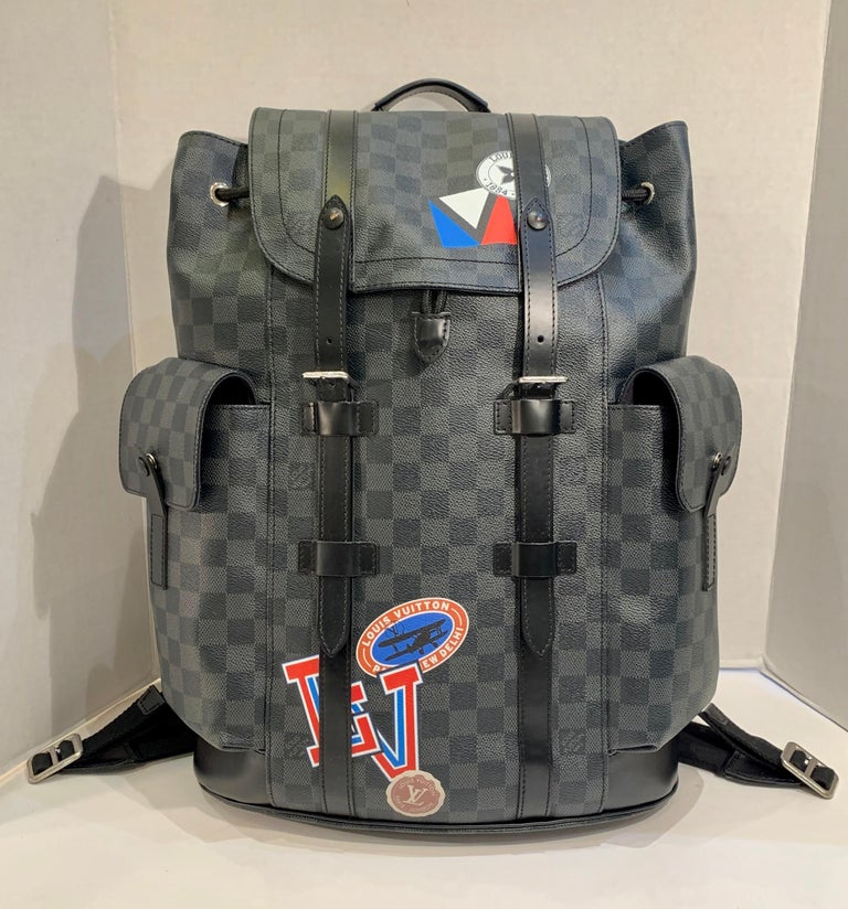 Rare and collectible, special edition, authentic LOUIS VUITTON Damier Graphite Christopher PM Backpack with Louis Vuitton un-customized factory retro style LV travel decals as part of the pattern is crafted of Louis Vuitton signature Damier black