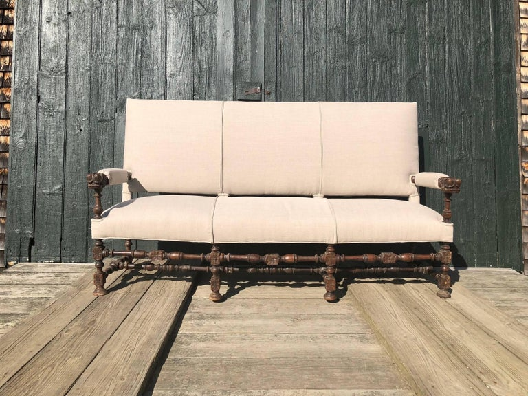 Unusual very early French sofa with rare Baroque stretcher form. Newly upholstered, this magnificent sofa offers a significant carved antique frame.