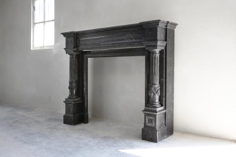 A special fireplace with many adaptations in the neoclassical style from the 19th century. The top has beautiful lines and various ornaments. The legs are partially round and equipped with flutes. A stately fireplace made of Belgian bluestone that