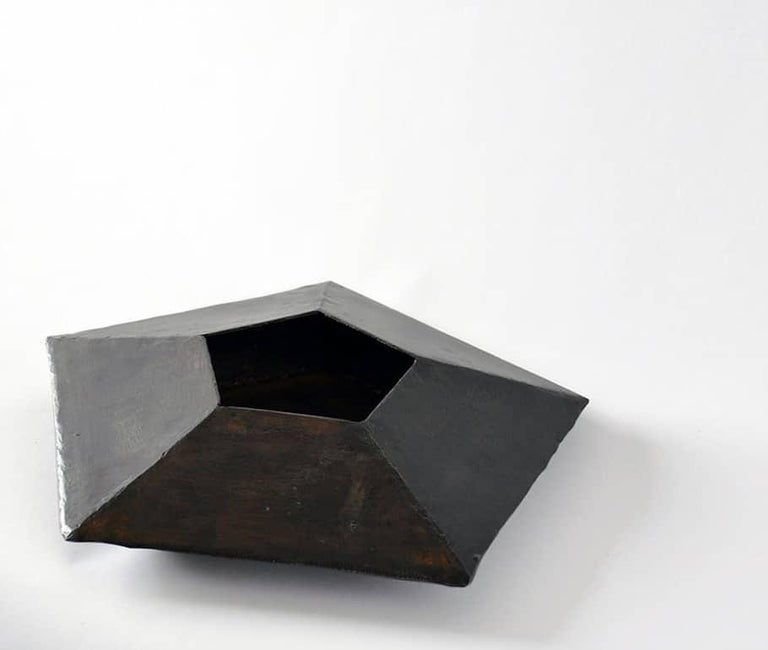 Ten facets form this unique object. Mathematically designed and hand-wrought.  Blackened steel, waxed finish, suede base.  Each vessel is unique and will vary slightly in size and shape from description.  Made in New York.