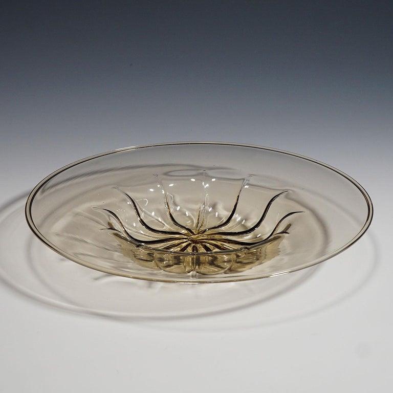 A 'vetro soffiato' glass plate in smoke-colored transparent glass, designed by Vittorio Zecchin in 1925 and manufactured by Venini, Murano Venice. acid stamped signature 'Venini Murano' on the base. Lit.: marino barovier, vittorio zecchin:
