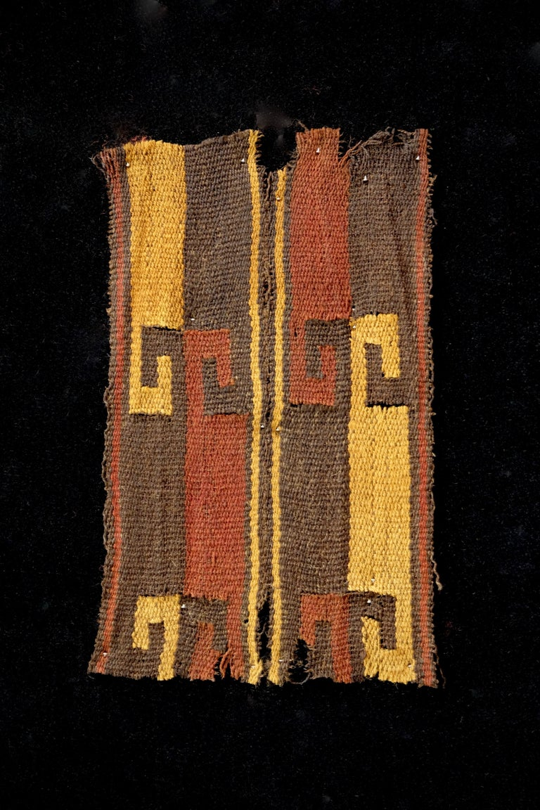 Brown, yellow and red wave like pattern textile fragment. Framed in a black shadowbox.  It is a wonder to behold antiquities such as a Pre-Columbian textiles, an authenticpiece of art that has been preserved for centuries and that survives