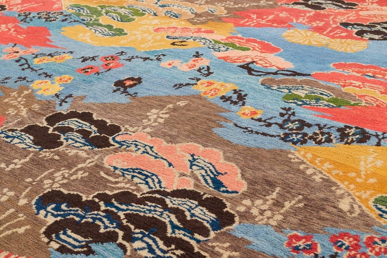 Delicate flowers and Eastern motifs are scattered throughout Mountain Blossom's vibrant composition. The field of brilliant blue sets off the multicolored designs in this all wool carpet. Original design by Joseph Carini. Measures: 9' x 12'.  This