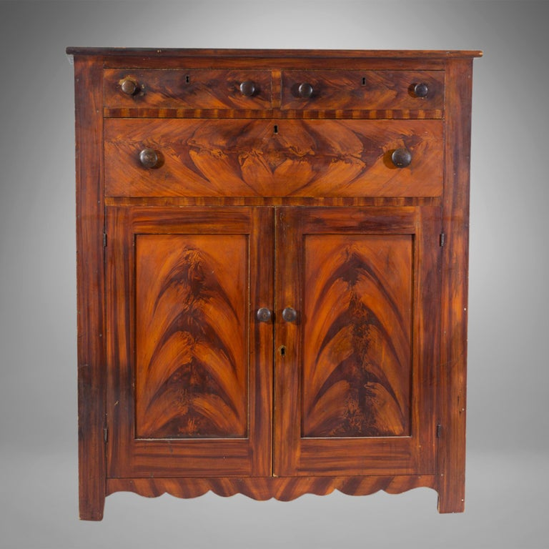 Configured with two short drawers over a long drawer above a pair of paneled doors with a scalloped apron and turned wooden knobs, standing on bracket feet, the faux painted decoration with yellow and ocher is original to the piece.