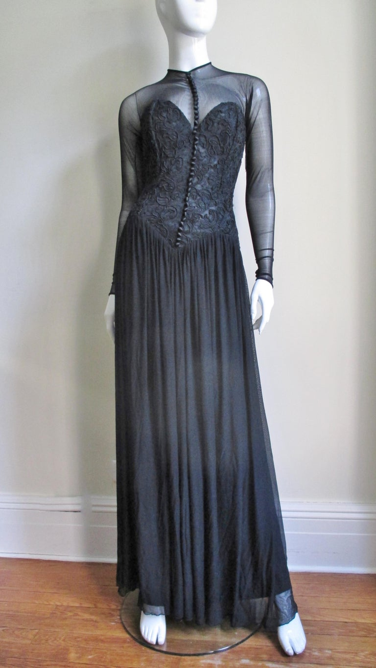A fabulous black dress gown from Vicky Tiel Couture.   It has a fitted boned bustier bodice covered in an intricate corded lace pattern with numerous front silk buttons and loops.  The mesh skirt is full and gathered and dress is striking with the