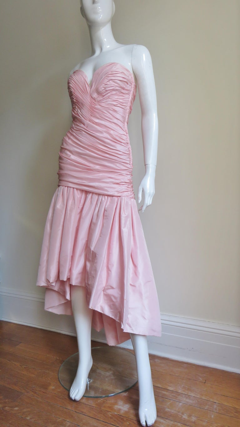 A great pink silk high low dress from Vicky Tiel.  The drop waist horizontally ruched strapless bodice has a front sweetheart cut neckline.  Onto the bottom of the bodice is gathered a full skirt knee length in the front, ankle length in the back.
