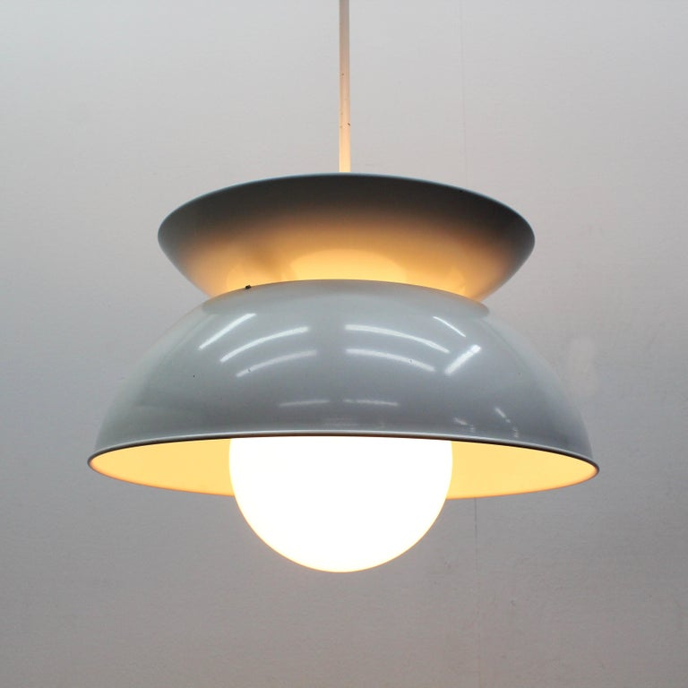 Cetra hanging lamp was designed by Vico Magistretti for Artemide in 1965. This lamp it is made of 2 bowls in white lacquered metal and one opaline glass ball. The upper bowl with 3 light bulbs functions as an uplighter, the opaline ball with 1