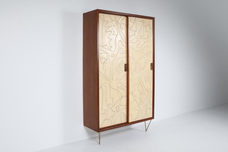 Victor Cerrato, cabinet, wood and brass, Italy, circa 1958.  This masterpiece is pure art, amongst our favorite pieces as of yet. The dresser has a solid mahogany frame, beech interior and is mounted on brass harpin legs. The two door panels are