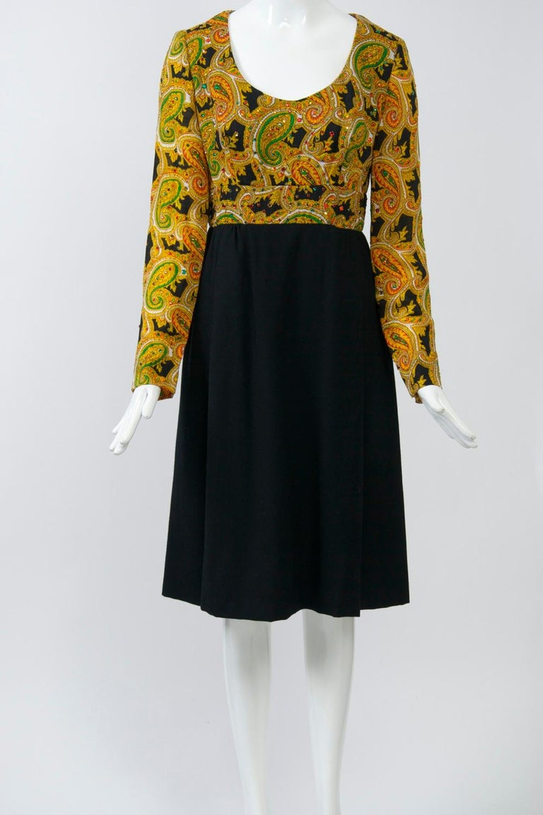 c.1970 dress by Victor Costa featuring a modified empire bodice of paisley wool challis has a scoop neck and is sprinkled with coordinating  red and green rhinestones. The set-in paisley waistband gives way to a black knit A-line skirt with soft