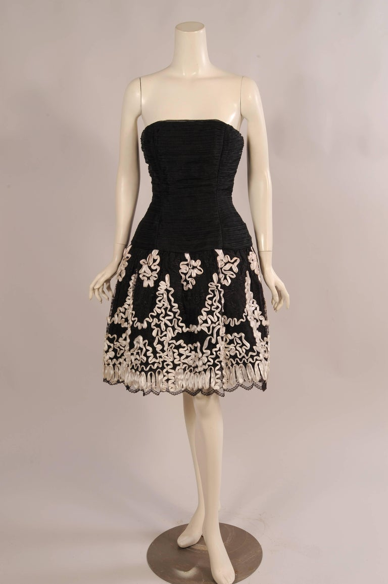 This flirty little evening dress was designed by Victor Costa for Saks Fifth Avenue. The strapless dress has a fitted organza bodice with a dropped waistline. The full skirt is black lace embellished with white satin ribbon soutache over an organza