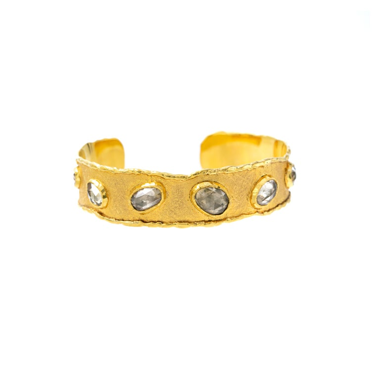 Inspired by the energy pulsating throughout nature, Velyan unites pure metals and gemstones into stunning styles that display the grandeur of fine jewelry.  This cuff bracelet features zircon stones set in 18k and 24k yellow gold.  Details: Zircon