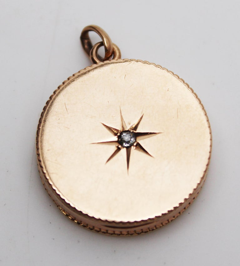 This is an elegant Victorian locket in 14k rose gold featuring a beautiful star set diamond in the center! The locket has a classic circular design featuring a subtly detailed border and an invisible hinge. The front of the locket is set with a