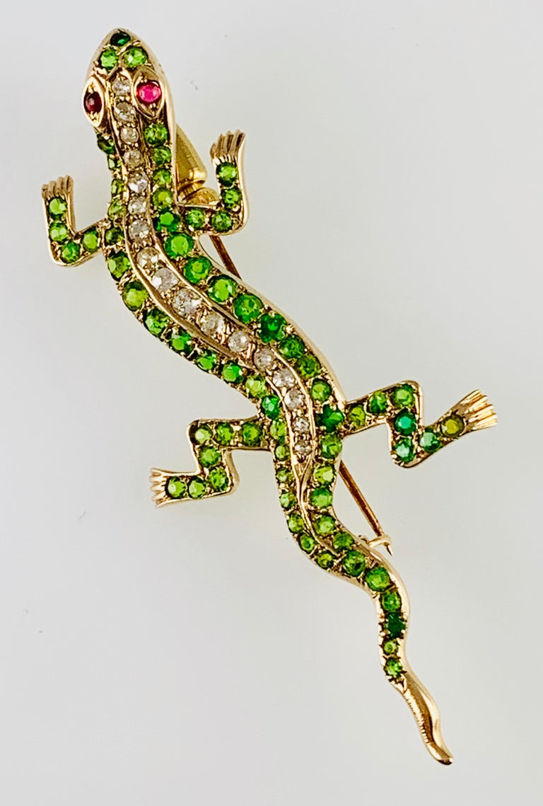 Gorgeous Victorian Diamond & Tsavorite Garnet Lizard Brooch! It is made in 14K Yellow Gold and contains 17 European Cut Round Diamonds accented by pave back tsavorite Garnets as well as Ruby eyes. It m measures 2.5 inches long by 1&1/8 inches wide