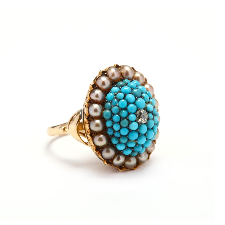 A Victorian 14 karat yellow gold bombe ring with a diamond, turquoise, and pearls. Centered on an old European cut diamond, surrounded by round cabochon cut turquoise stones and a halo of split pearls.  Stones: - diamond, 1 stone - old European