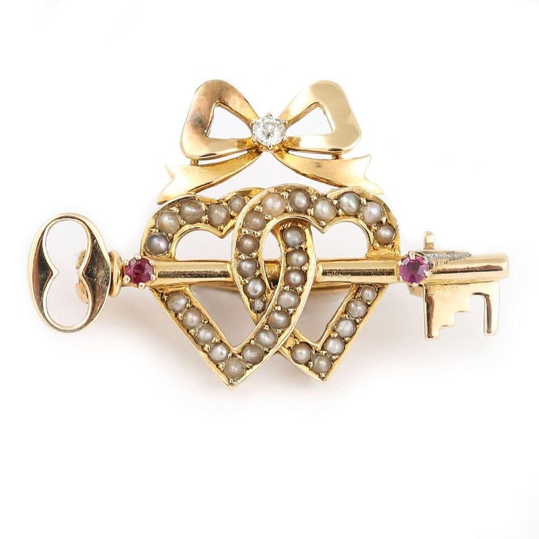 A beautiful Victorian 15 karat yellow gold sentimental brooch. It comprises a pearl double sweet heart, ruby set key and a diamond set bow. A brooch truly loaded with symbolism, this fine and impressive antique sweet heart brooch boasts two split