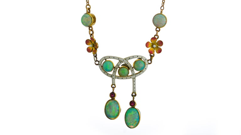 Art Noveau 18kt gold opal necklace, with natural opals and rubies, and enamel decoration. Made in England, Circa 1910. Tested positive for 18kt gold.  Dimensions -  Weight : 10 grams Necklace Length: 40.5 cm Pendant Size: 6.7 x 3.2 cm  Opal -  Cut: