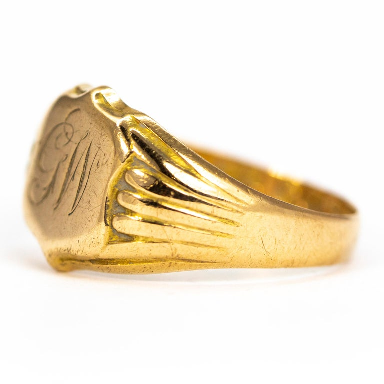 The fluid scroll font which reads 'GW' is finely engraved onto the main shield panel of this ring. The chunky shoulders have ribbed detail and carry on down into a plain band modelled in 18ct gold. Made in Birmingham, England.  RIng Size: R 1/2 or 8