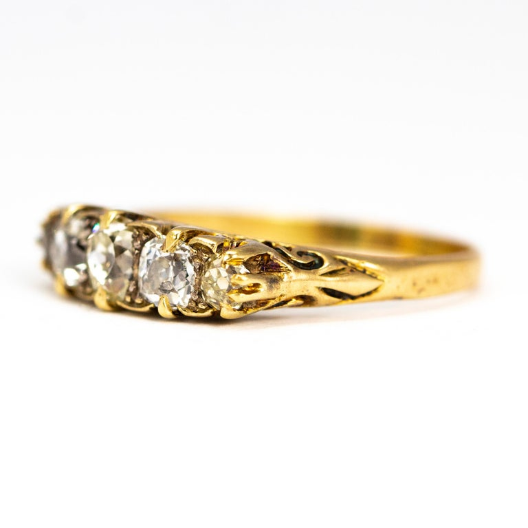 This ornate five stone ring shows off old cut diamonds totalling 1 carat. These stones are then wonderfully flattered within a beautifully delicate carved shank.  This handmade mount uses 18 carat Yellow Gold to compliment the craftsmanship of this