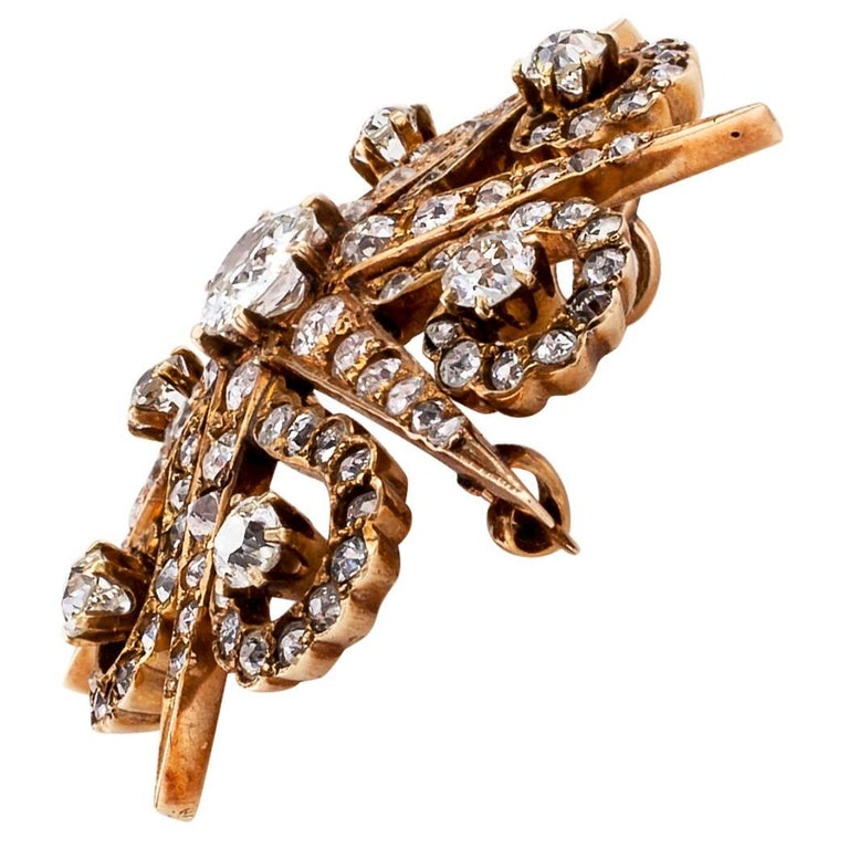 Victorian 1870s diamond and gold starburst brooch pendant. The antique six pointed star design with radiating curls of diamond light is set throughout with one hundred fifteen old mine-cut diamonds totaling approximately 4.50 carats, approximately H