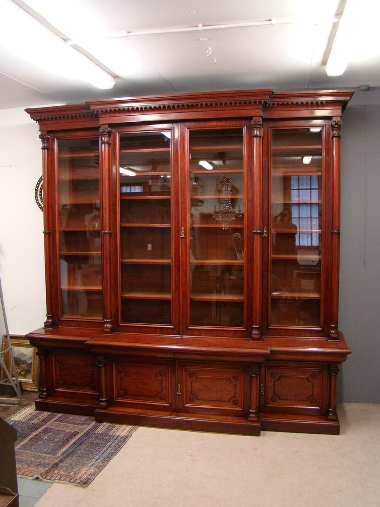 Exhibition quality Victorian 4-door breakfront mahogany bookcase, circa 1890. Surmounted by a tiered moulded cornice with a Gothic apron over 4 tall glazed doors, separated and flanked by Doric columns and opening to adjustable shelving. The base