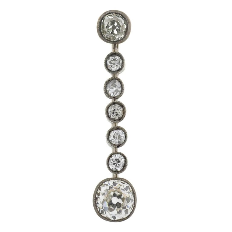 An exquisite pair of diamond drop earrings from the Victorian (ca1880) era! Crafted in 14kt yellow gold topped with sterling silver, each stunning earring adorns a sparkling row of old Mine Cut diamonds. Resting at the base is the largest diamond,
