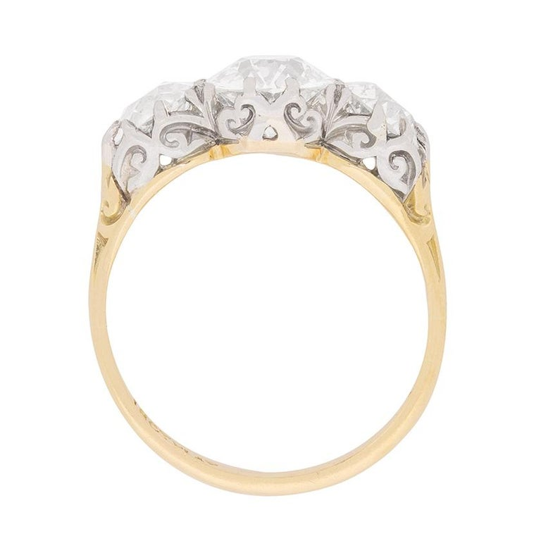 This rare and original Victorian era engagement ring, which dates back to the 1880s, showcases a gorgeous triad of old cut diamonds within an exquisite handmade setting.  These antique diamonds, which totals a substantial 3.80 carats! There is 1.00