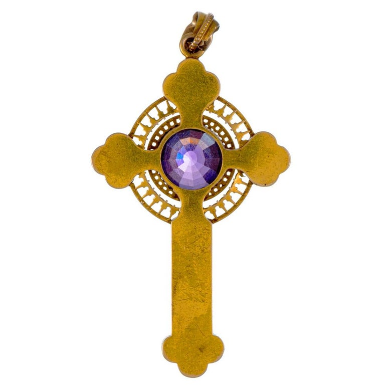 A glorious antique treasure for the devoted, the cross is rendered in 15k yellow gold and boasts a large faceted center amethyst framed by an intricate mounting of white enamel set upon a golden backdrop. The pendant measures 2.75 by 1.5 inches and