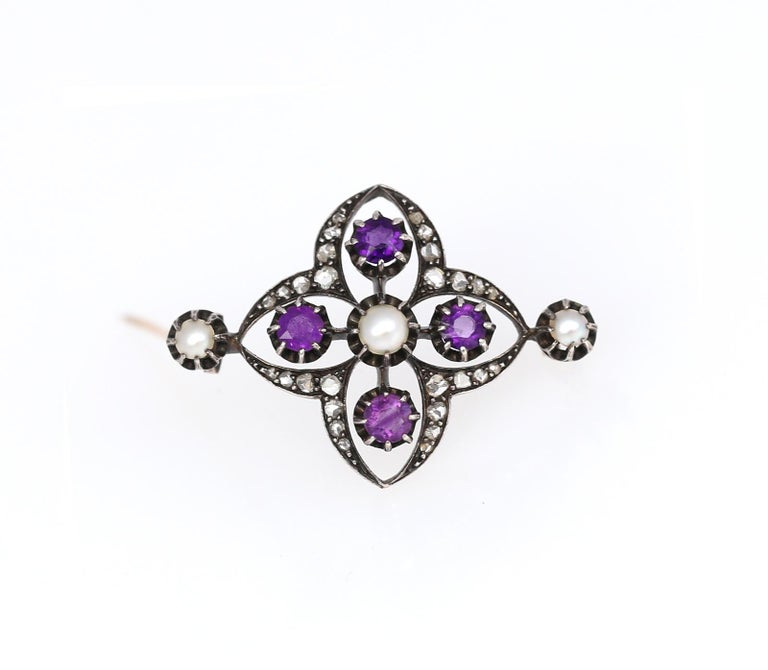 Late Victorian Brooch with four bright Amethysts, three fine Pearls and Rose-cut Diamonds. Set in Silver and Gold. Shaped in natural organic form resembling a flower, yet made in 1900 it has fine geometrical proportions.  Once it was common to
