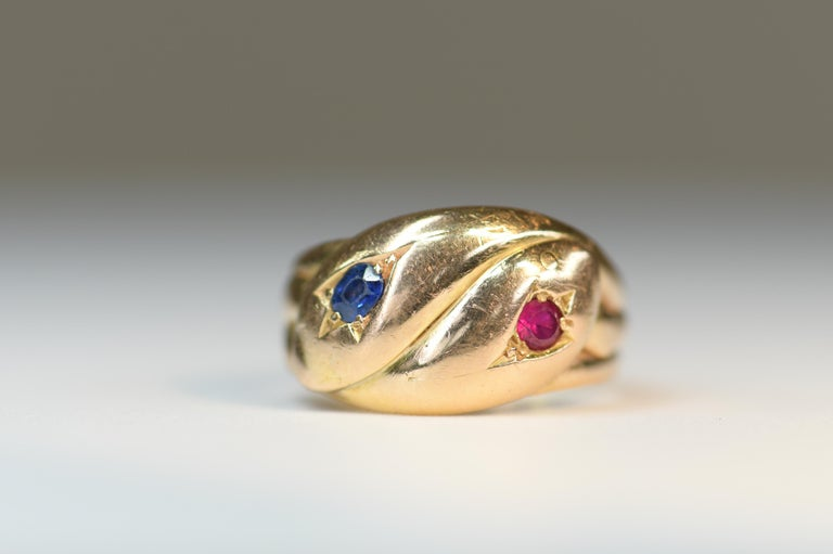 Stunning antique victorian double snake serpent ring. 2 yellow gold snakes entwined together with ruby and sapphire gem set heads.  Snakes are a symbol of everlasting eternal love, and became quite popular in the 1800's when Prince Albert presented