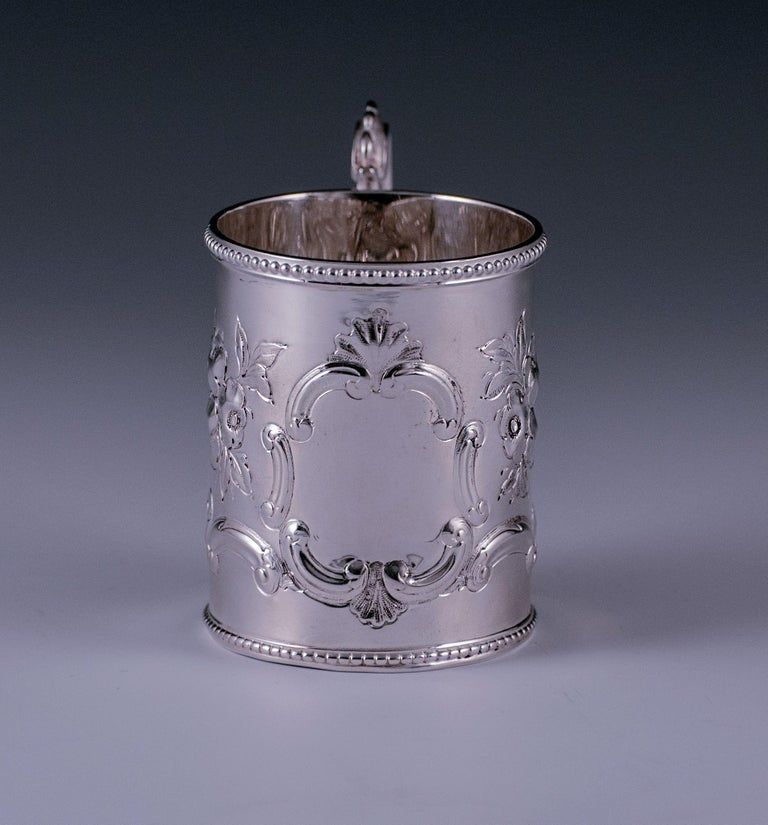 This fine Victorian antique sterling child's / christening mug are of tapering cylindrical form. The body is embossed with flowers, leaves and scrolls. On the side opposite the handle is a plain cartouche surrounded by scrolls and shells. The upper
