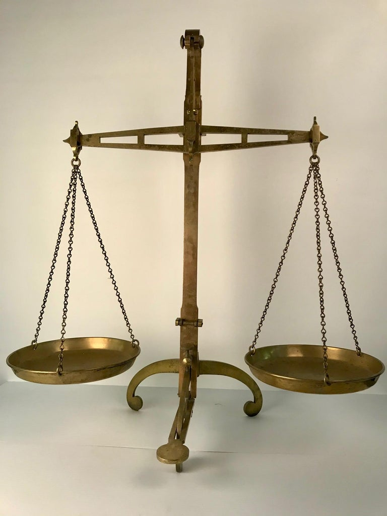 This is a mighty contraption for weighing specie and gold in quantity. It stands on three scrolling feet. It has a blocking and unblocking mechanism, so it can be moved with less difficulty. It is made entirely of brass including pans and chains.