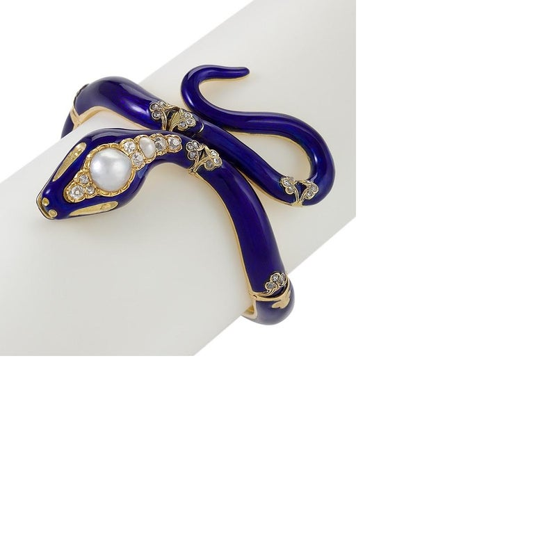 A Victorian gold and blue enamel snake bracelet with diamonds and pearl. The old mine-cut diamonds have an approximate total weight of .40 carat. After Prince Albert gave Queen Victoria a snake band with an emerald head as a wedding present in 1839,