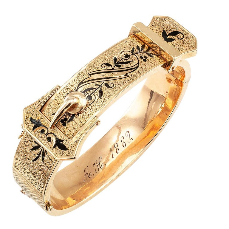 Victorian enamel and gold hinged buckle bangle circa 1882. The 14-karat gold buckle design is entirely decorated with chase work accented on the top and bottom halves with scrolling motifs and black enamel garlands, attached safety chain with jump