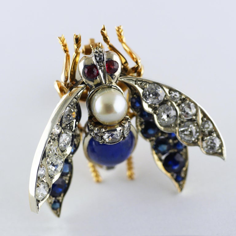 An exceptional, exquisite and well preserved Victorian brooch in the form of a bee with ruby eyes, sapphire and diamond wings, natural pearl and cabochon natural untreated Burma Sapphire.  Mounted in 18ct rose gold and silver set, intricately formed
