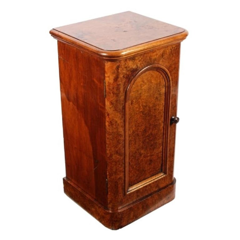 A middle of the 19th century Victorian burr walnut veneered bedside cabinet.  The cabinet has a left hand opening door, a rounded edge to the top and a moulded frame.  The door has an original ball catch fastening and the interior has a single