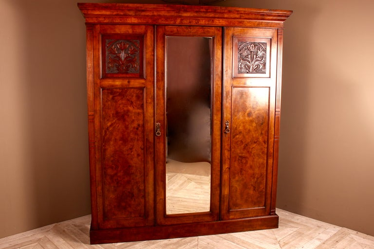 A lovely Victorian burr walnut compactum wardrobe. The flared cushion cornice sits above three panelled doors. The centre mirrored door being flanked by two wardrobes, the doors being topped with nicely carved flowers and foliage. To the outside of