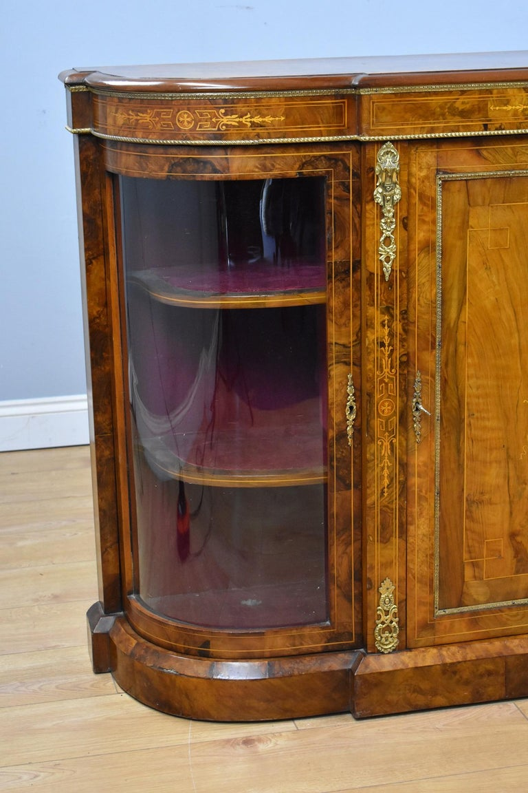 Victorian burr walnut inlaid credenza in good condition. The credenza has a decorative inlay to the centre door when opened encloses a single shelf with inlay to the sides and outer edge, it has decorative brass to the top and Ormolu mounts with a